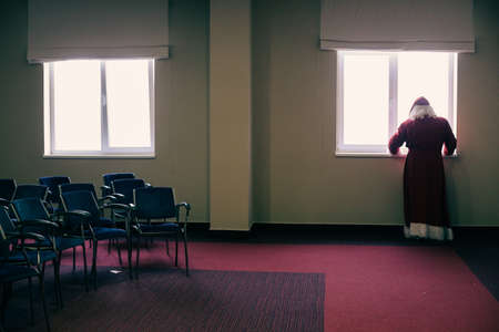 A person dressed as Santa Claus watches on the window inside an empty office room. Sad Santa.