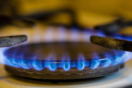 Shallow depth of field (selective focus) image with a burning old traditional gas stove top. 免版税图像