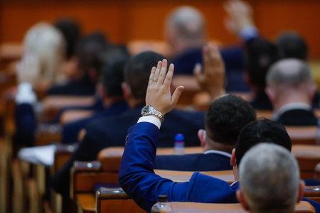 Bucharest, Romania - December 22, 2020: Romanian deputies vote bills by raising their hands in a full Chamber of Deputies meeting.