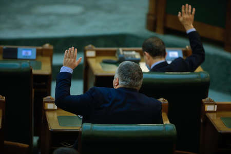 Bucharest, Romania - December 22, 2020: Romanian senators vote bills by raising their hands in a full Senate meeting.