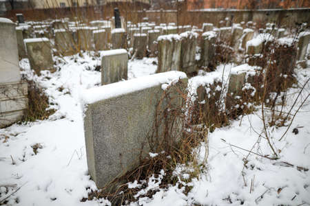 Tombstones in a jewish cemetery during a cold and snowy winter day.