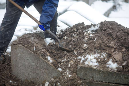Details of a gravedigger covering a tomb with dirt with a shovel during a burial ceremony on a cold and snowy winter day. Standard-Bild