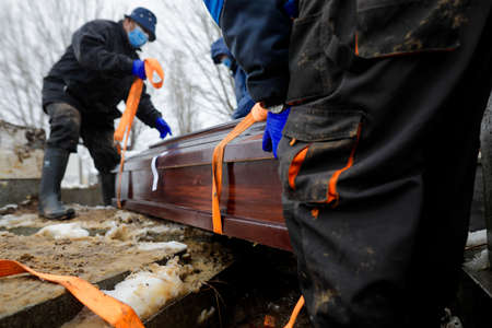 Shallow depth of field (selective focus) with undertakers burying a coffin containing a victim    on a cold snowy winter day. Standard-Bild