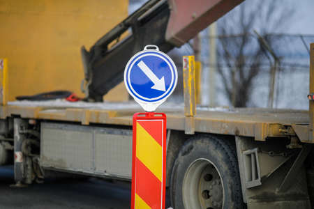 Shallow depth of field (selective focus) with a road attention and go right sign on a heavy traffic road.