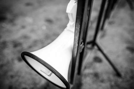 Shallow depth of field (selective focus) with a bullhorn hung on a metal fence during a political/social issues rally.