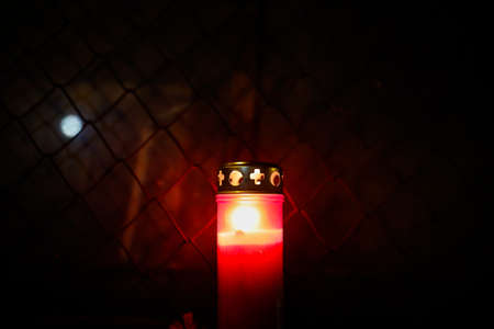 Burning candle in front of a metallic net during the night. Standard-Bild