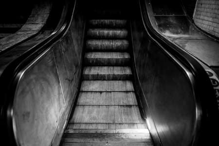 Black and white image with a dirty and dark escalator on a cold urban night. Standard-Bild