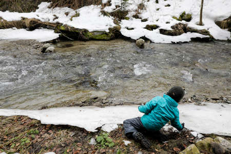 Young boy playing near a mountain stream during a snowy winter day in the Romanian Carpathian Mountains. Standard-Bild