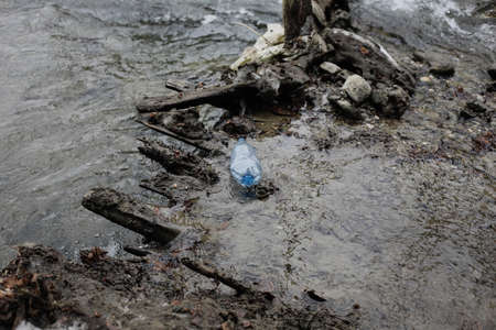 Plastic bottle on a running mountain stream during a cold and sunny winter day in the Romanian Carpathian Mountains. Standard-Bild