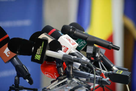 Bucharest, Romania - March 23, 2021: Shallow depth of field (selective focus) image with  microphones from various Romanian news televisions before a press conference.