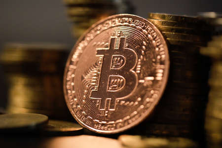 Shallow depth of field (selective focus) image with a Bitcoin metal coin near other metal coins - cryptocurrency concept. Standard-Bild