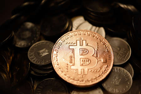 Shallow depth of field (selective focus) image with a Bitcoin metal coin on top of other metal coins (Romanian RON) - cryptocurrency concept.