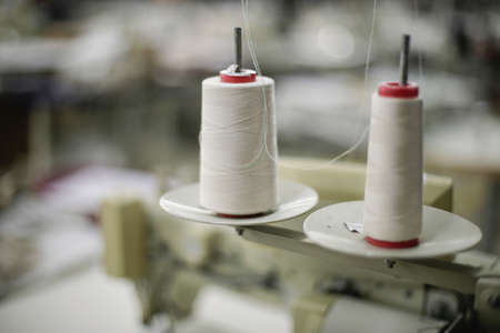 Shallow depth of field (selective focus) image with thread spools in a textile factory. Standard-Bild