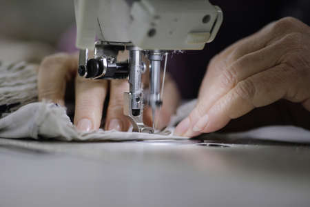 Shallow depth of field (selective focus) image with the hands of a senior woman working at an electric sewing machine in a textile factory.