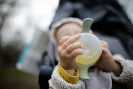 Shallow depth of field (selective focus) image with the hands of a baby boy holding a baby bottle.