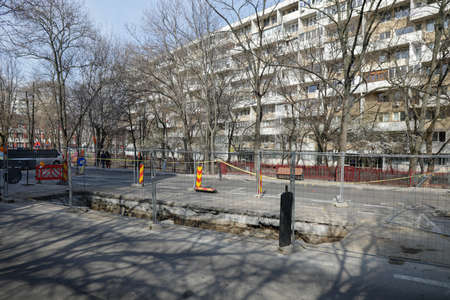 Bucharest, Romania - March 28, 2021: Big hole in the road for workers to repair a RADET pipeline in Bucharest.