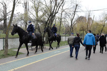 Bucharest, Romania - March 28, 2021: Romanian jandarmi on horses patrol the IOR park in Bucharest during Covid-19 pandemic restrictions.