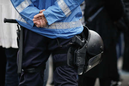Bucharest, Romania - April 3, 2021: Details with the riot kit of a Romanian jandarm during a rally: gun, helmet, radio station, baton. Editorial