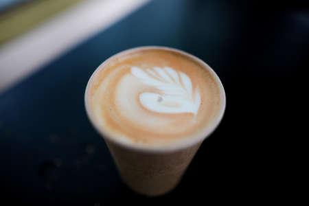 Shallow depth of field (selective focus) image with details of a decorated coffee in a paper cup. Standard-Bild