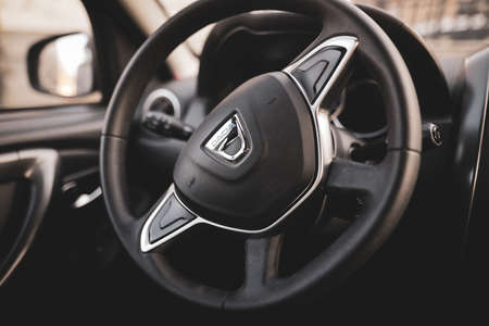Bucharest, Romania - April 11, 2021: Shallow depth of field (selective focus) image with the Dacia logo on a Duster steering wheel.