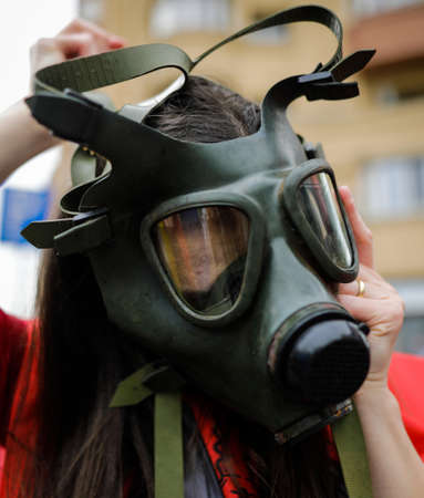 Shallow depth of field (selective focus) image with an old and worn out military gas mask without filters on the face of a woman.