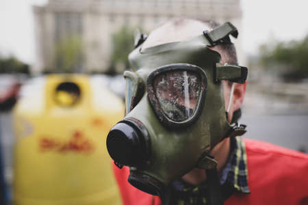 Shallow depth of field (selective focus) image with an old and worn out military gas mask without filters on the face of a man.