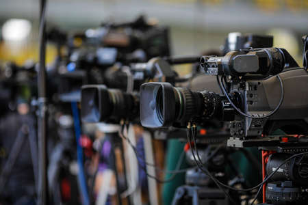 Bucharest, Romania - April 25, 2021: Shallow depth of field (selective focus) image with TV cameras on tripods on a press event.