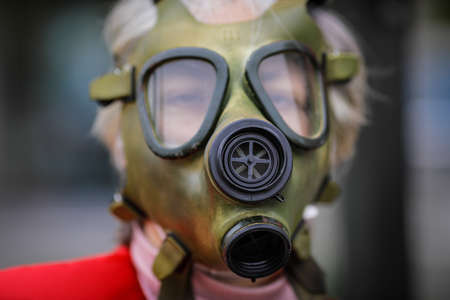 Shallow depth of field (selective focus) image with an old and worn out military gas mask without filters on the face of a senior woman.