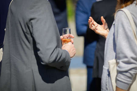Details with a man and a woman interacting at a classy event, while holding a glass of wine.
