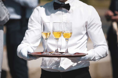 Shallow depth of field (selective focus) details with a waiter walking around and giving sparkling wine to the guests of an event.