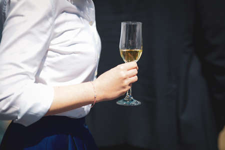 Details with the hands of a woman interacting at a classy event, while holding a glass of wine. Standard-Bild