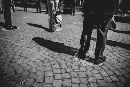 Shallow depth of field (selective focus) details with feet of people standing on special spots for social distancing at an event, during the Covid-19 outbreak.