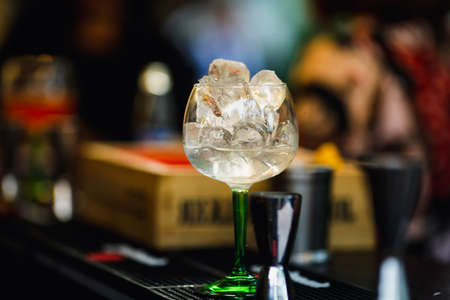 Shallow depth of field (selective focus) image with a glass with ice cubes and vodka on the counter of a bar.