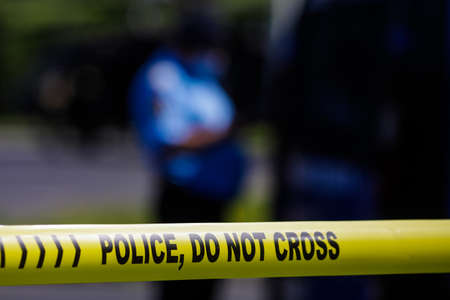 Shallow depth of field (selective focus) image with Police plastic tape reading Police, Do not cross, at a crime scene.