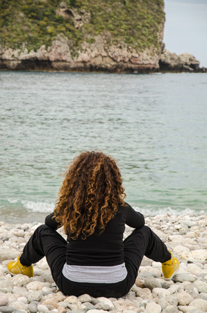 Mature Woman on vacation, go to the beach to find herself, with meditation, relaxation, solitude. photo