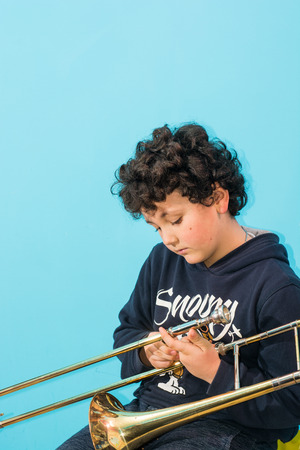 dedication: child is Exercised by the trombone, with dedication, concentration, commitment.
