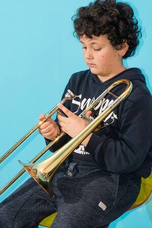 trombon: ni�o es ejercido por el tromb�n con el compromiso de dedicaci�n de concentraci�n. Foto de archivo