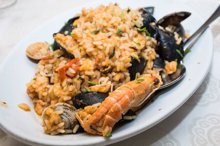 pics: A dish of  seafood rice pics, with mussels, clams, shrimp, mussels, ready to eat, in a table spread. Stock Photo