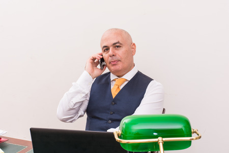 conscientious: A business man on the phone and pc, at desk, in conference call and bald. An antique desk and important.