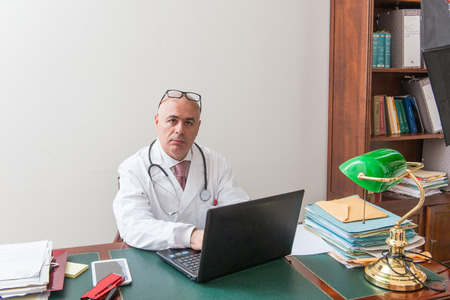 registering: Doctor in his studio at desk, on pc,  with glasses. Use new technologies. In his professional studio, he is sitting at antique desk, and a green lamp shade of green. Stock Photo