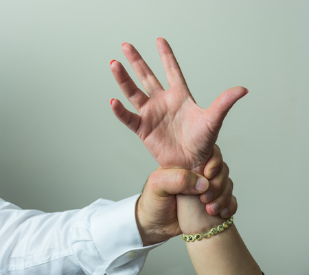 abductor: Abductor, forcefull man's hand on a female, imposing his will on a woman or girl friend. Stock Photo
