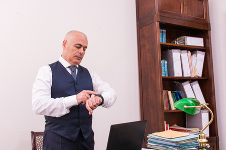 shirtsleeves: A businessman uses smartwacth pic, at desk, at work, in shirtsleeves, in his professional studio, with hands and fingers. Stock Photo