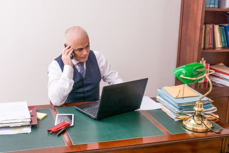 A business man on the phone and pc, at desk, in conference call and bald. An antique desk and important.