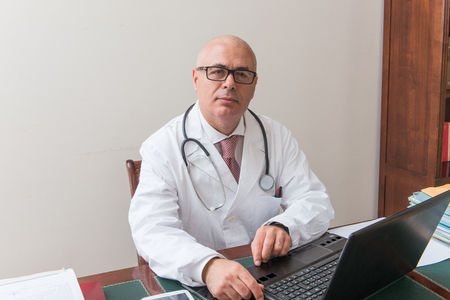 Doctor in his studio at desk, on pc,  with glasses. Use new technologies. In his professional studio, he is sitting at antique desk, and a green lamp shade of green. Stock Photo