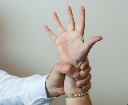 cowardly: Abductor, forcefull man's hand on a female, imposing his will on a woman or girl friend. Stock Photo