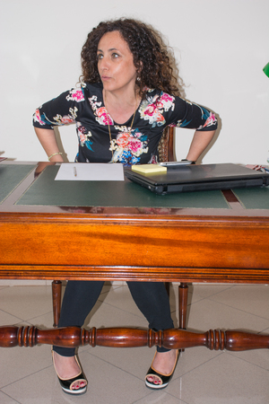 intriguing: Modern woman, working in her office. Use the tools of modern technology, keeping pace with modern times. An antique desk in wood. Stock Photo