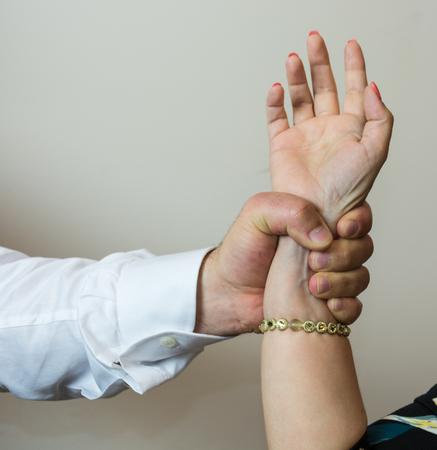 violencia intrafamiliar: Abductor, forcefull sirve la mano de una mujer, imponiendo su voluntad sobre una amiga o una niña. Foto de archivo