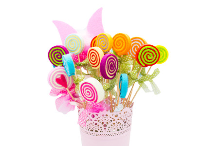 ingenuity: Vase of fake flowers with different colors. Delight in a basket. Felt, the result of ingenuity and creation. Bright colors and festive, lollies in a basket.