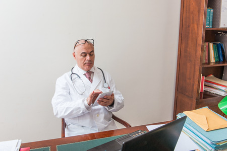 registering: Aback doctor in his studio,  uses a tablet in front of his laptop. Use new technologies. In his professional studio, he is sitting at antique desk, and a green lamp shade of green. Stock Photo