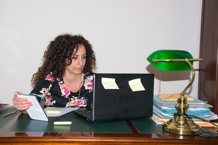 hair blacks: Modern woman, working in her office. Use the tools of modern technology, keeping pace with modern times. An antique desk in wood. Stock Photo